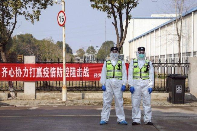 武漢警察著防護衣於隔離點外站崗。 美聯社