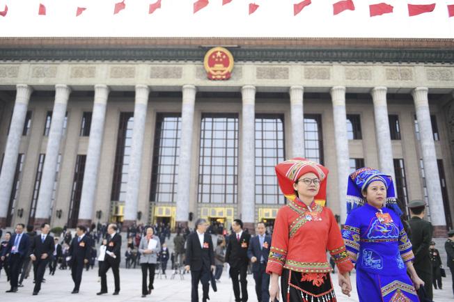 中國一年一度的全國人大、政協會議因新冠肺炎疫情而延期。圖為多名人大代表走出北京人民大會堂。(中新社)