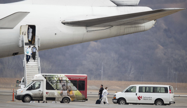 """美国政府专机接返困在日本横滨码""""钻石公主号""""邮轮上的300多名美国公民游客,17日清晨降落在内不拉斯加州的奥马哈机场,陆续下机。(美联社)"""