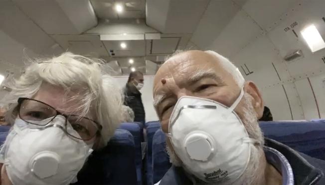 「鑽石公主號」郵輪上的美國公民遊客莫列斯基夫婦(Paul Molesky),在返美專機上戴著口罩自拍。(美聯社)