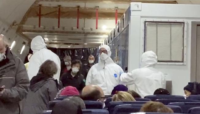 美國政府專機接返困在日本橫濱碼「鑽石公主號」郵輪上的300多名美國公民遊客。他們17日晨在東京羽田機場登機前,聽取穿上防護衣的醫療專家解說。(美聯社)