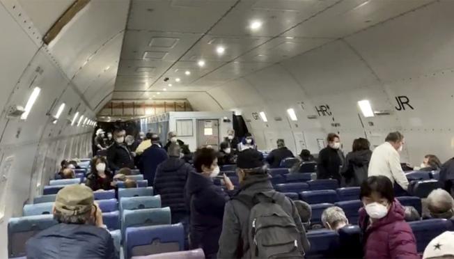 """美国政府派出专机接返困在日本横滨码""""钻石公主号""""邮轮上的300多名美国公民游客。图为专机内的乘客。(美联社)"""