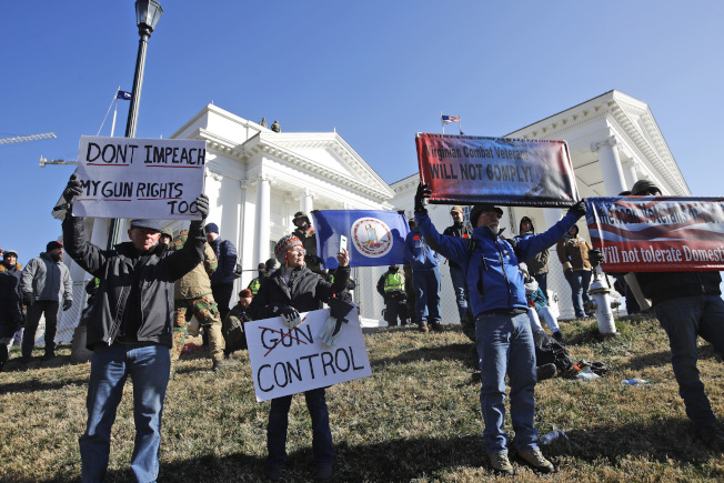 擁槍人士在維吉尼亞州州議會大廈前舉支持擁槍標語。(美聯社)