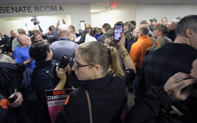 民主黨的維吉尼亞州長諾譚推動禁止銷售攻擊武器的法案,17日在州參議會司法委員會審議時受阻,法案將擱置一年。圖為在場擁槍人士慶祝表決結果。(美聯社)