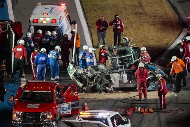 賽車手紐曼(Ryan Newman)發生意外後,救護人員和NASCAR人員趕緊上前將紐曼從冒煙的車身拉出來。(路透)