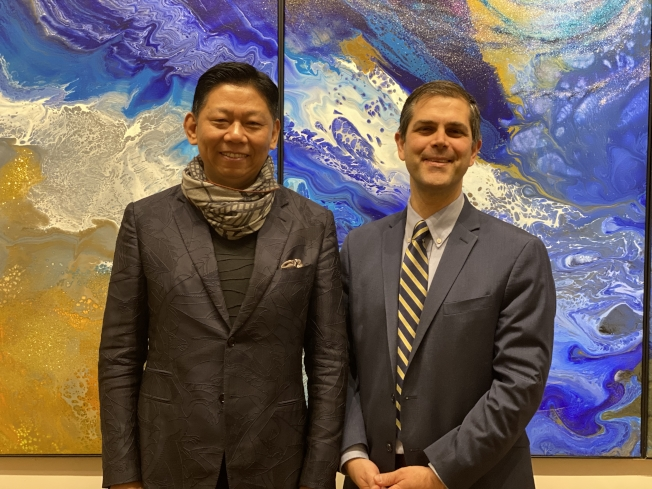 曹俊(左)與黑爾(右)在他的畫展作品前合影。(記者牟蘭/攝影)
