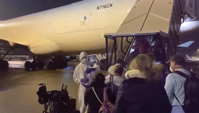 美國政府專機接返困在日本橫濱碼「鑽石公主號」郵輪上的300多名美國公民遊客,17日清晨降落在不拉斯加州的奧馬哈機場,陸續下機。(美聯社)