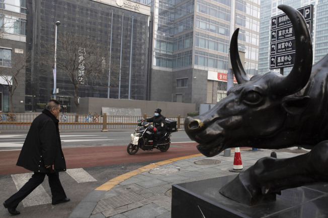 中國遭到新型肺炎疫情衝擊,實施居家隔離,不僅消費銳減,百業蕭條,同時復工無期。圖為北京的商店前,正進行消毒。(美聯社)