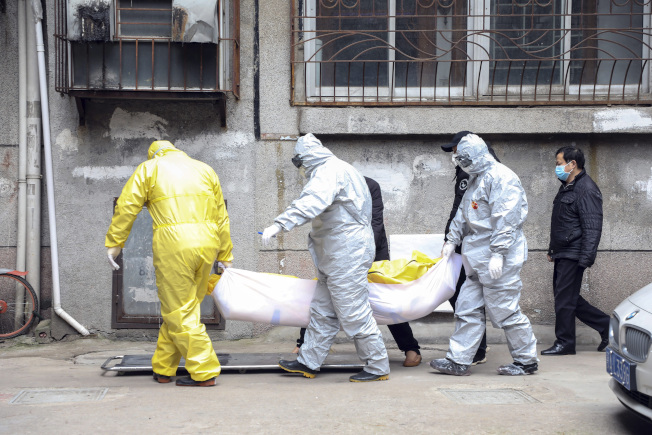 在處理新冠肺炎逝者遺體時,武漢殯葬業者均穿上防護衣進行作業。美聯社