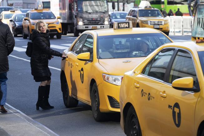 紐約,一位乘客正準備上計程車。(美聯社)