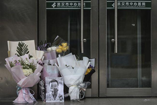 圖為武漢市中心醫院眼科醫生李文亮於2月7日病逝,多位市民來到這位「疫情吹哨人」所在的醫院獻花悼念。(Getty Images)