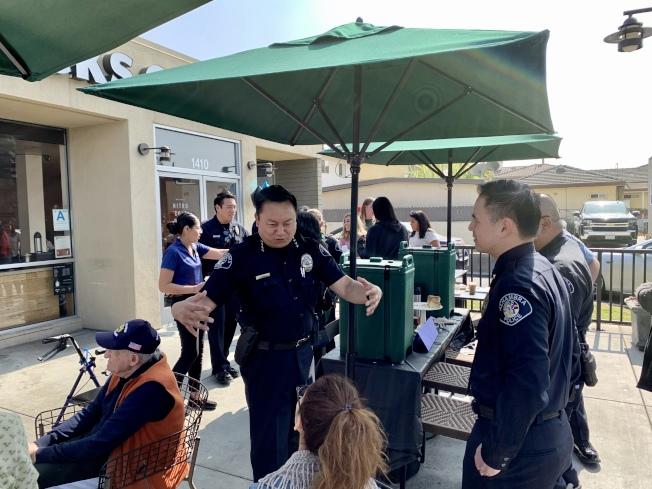 阿罕布拉市警局19日在星巴克請市民喝咖啡,並做治安宣導工作。圖為阿市警局局長Timothy Vu(左)與民眾互動。(記者陳開/攝影)