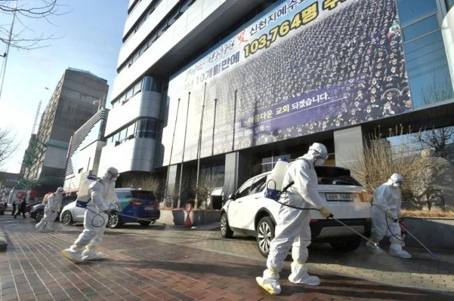 圖為南韓派員在第31號確診病例做禮拜的教堂前方街道進行消毒工作。路透