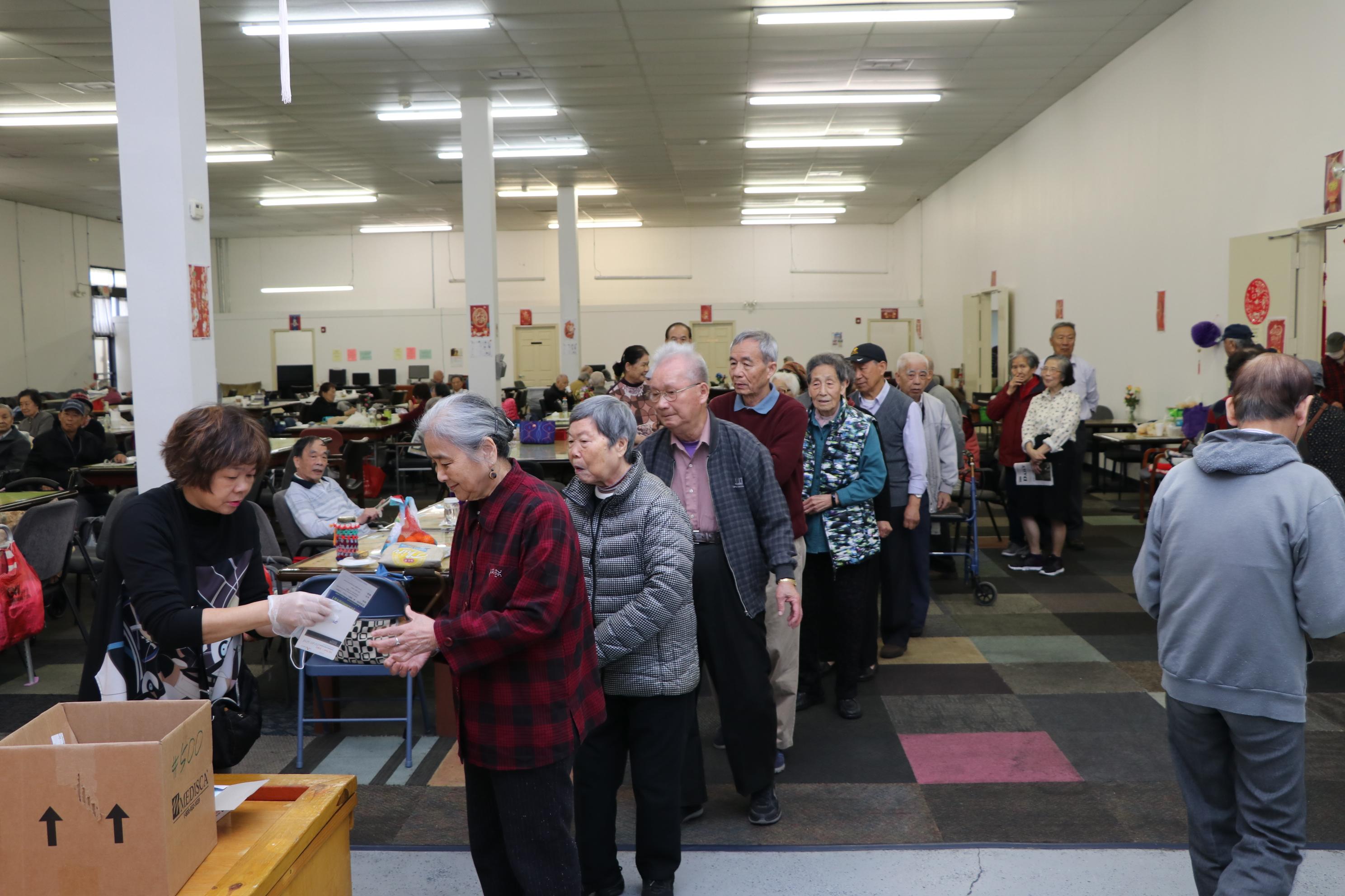 美福保健藥局的工作人員熱心地為陽光活動中心的老人家送上口罩,老人家都很開心。(記者封昌明/攝影)