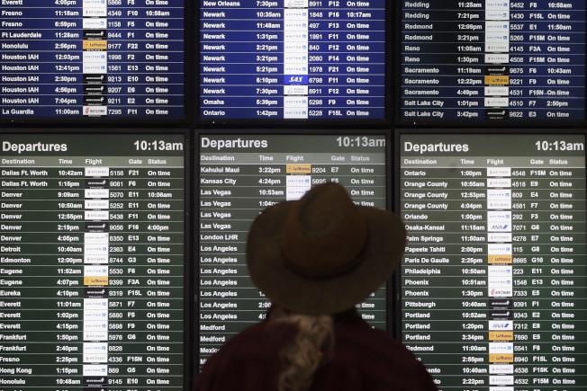 2019年來國內飛行旅客飽受誤點和飛行時間被延長的困擾。圖為旅客查看班機資訊。(美聯社)