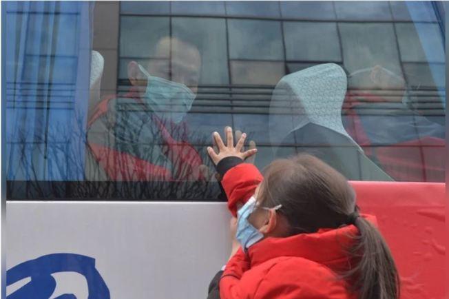 官方一篇論文披露,早在1月20日前,已出現近6000名病人。圖為醫護人員和女兒隔著車窗道別。(中新社)