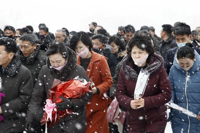 北韓的疫情到底如何?專家憂慮情況恐比中國嚴峻。圖為2月16日向北韓已故領袖金日成及金正日獻花致意的民眾。(美聯社)