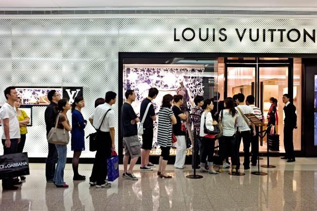 中國今年第1季消費受疫情影響最大,3月消費市場有望觸底回穩。圖為中國消費者排隊進入上海購物中心路易威登(LV)門市。(Getty Images)