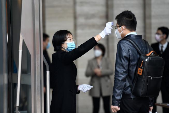 圖為廣東深圳辦公大樓為了防疫,替出入人員量體溫。(新華社)