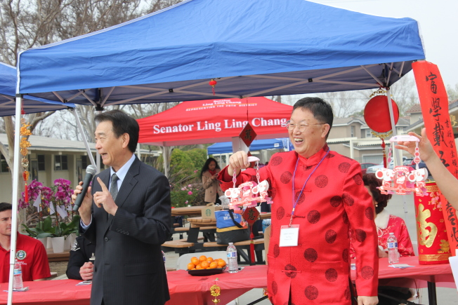 橙僑中心主任蔣翼鵬(左)向主辦方頒發賀狀。(富樂頓中文學校提供)