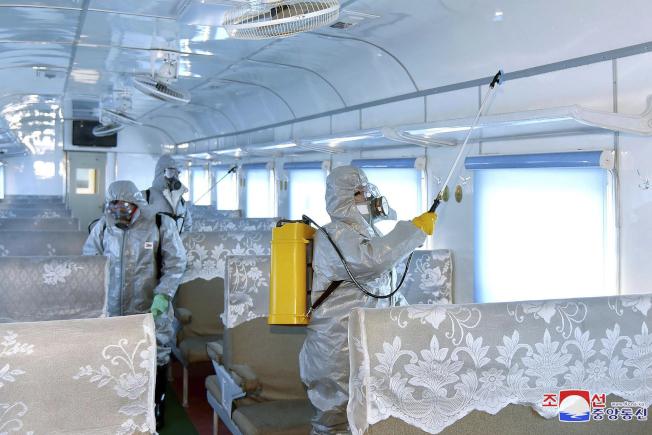 北韓身穿防護衣人員在公共場所消毒。(美聯社)