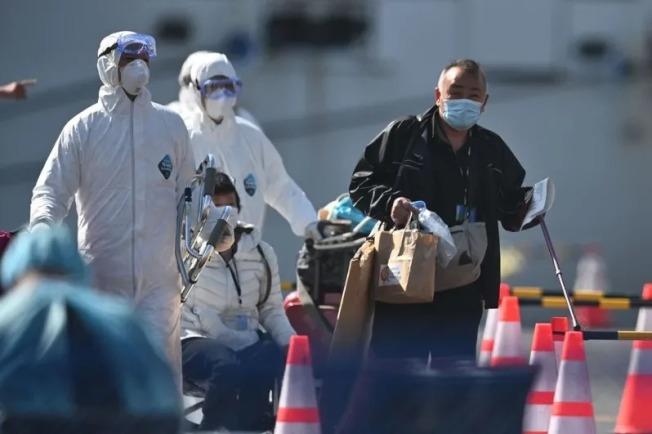 圖為鑽石公主號郵輪乘客完成隔離檢疫以後下船。(Getty Images)
