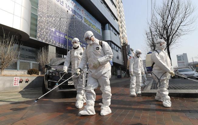 南韓發生新冠肺炎社區傳播,圖為穿上防護服的工作人員在大邱一所教會前面消毒。(美聯社)