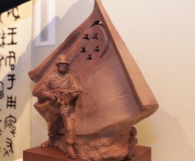 新加坡德光島軍人持槍站在飄揚國旗下蓄勢待發的巨型雕塑,是台灣雕塑家陳連山作品,圖為陳連山展出這座原創版「國民服役」雕塑模型。中央社