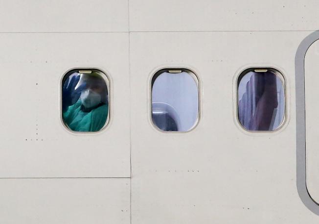 從日本撤僑包機21日晚間返抵桃園機場,飛機停妥後,旅客隔著機窗玻璃向採訪的媒體記者揮手。記者陳嘉寧/攝影