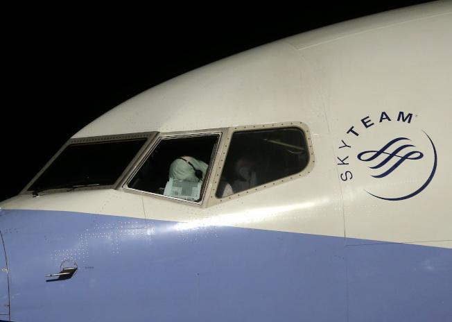 從日本撤僑包機21日晚間返抵桃園機場,隔著駕駛艙玻璃可以發現,機長全身包裹著防護衣操作飛機。記者陳嘉寧/攝影
