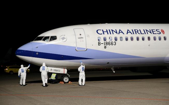 從日本撤僑包機返抵桃園機場,飛機停妥後,穿著防護衣的地勤及機務人員,環繞機身前後,執行落地後例行性安全檢查。記者陳嘉寧/攝影