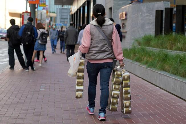 儘管港府多次澄清米麵、厠紙等日用品貨源充足,但仍有市民搶購。圖為一名婦女21日手拎3條共36卷厠紙走在北角街頭。(中通社)