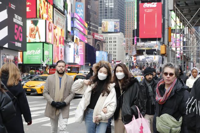 葛謨重申紐約州對以疫情為藉口而歧視、攻擊華人的行為絕不容忍。圖為兩名戴口罩的亞裔民眾在時報廣場。(中新社)