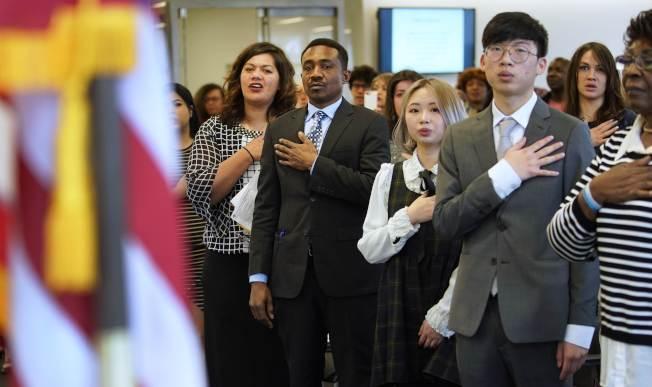 川普政府不准造成公共負擔的移民入境,24日開始實施。圖為來自各國的移民宣誓入籍。(Getty Images)