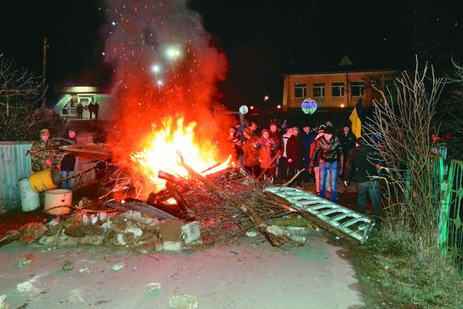 烏克蘭新桑扎里鎮民眾,企圖以路障阻止從武漢撤回的民眾在當地隔離。(路透)