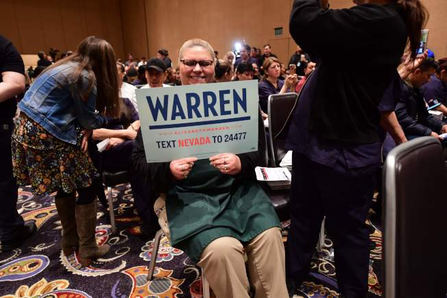 在黨團會議開始前,參議員華倫的支持者舉起標語。(Getty Images)