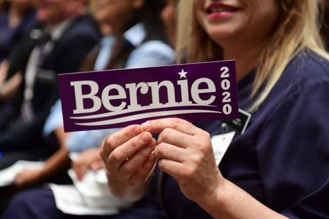 在黨團會議開始前,參議員桑德斯的支持者舉起標語。(Getty Images)
