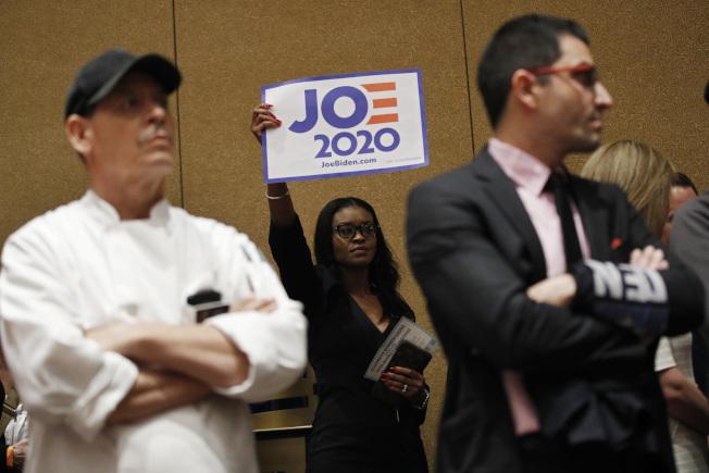 在黨團會議開始前,前副總統白登的支持者舉起標語。(美聯社)