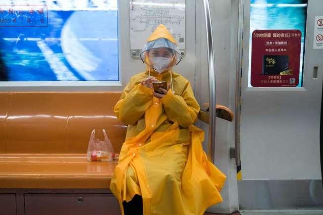 疫情嚴峻,北京沒有什麼人敢搭地鐵,這一位例外,但她卻穿上全副裝備。(美聯社)