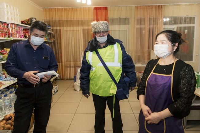 在俄國烏拉區的凱薩琳堡市內開業的中餐館員工(右)都要戴口罩。當地哥薩克人員(左)在過去三周,每周二次巡邏大街,專找中國人,送上口罩,努力防疫。(美聯社)