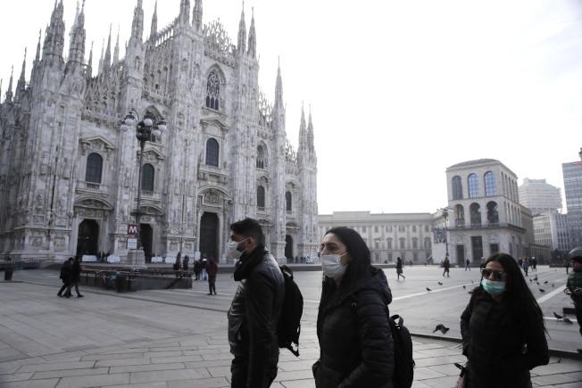 義大利米蘭主教座堂前許多民眾23日戴上口罩。義大利新增多起無國外旅遊史新冠肺炎病例,當局已下令封鎖12座城鎮。(美聯社)