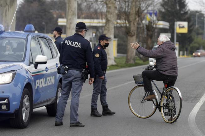 義大利當局為防止病毒疫情擴大,下令封鎖全國十多個城鎮進出要受管制。圖為 北部小城卡薩布斯特林戈,有警察駐守。(美聯社)