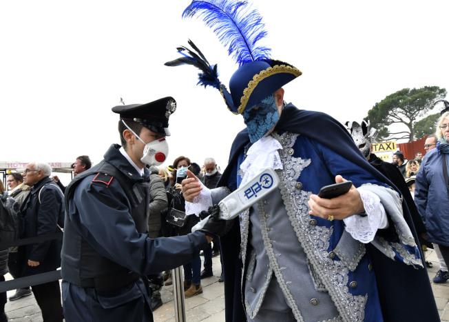 受到突如其來的病毒影響,行之有年的義大利嘉年華會被迫臨時中止。23日街上的警方都戴上口罩執行,面具與口罩一時分不清何者是遊客。(美聯社)