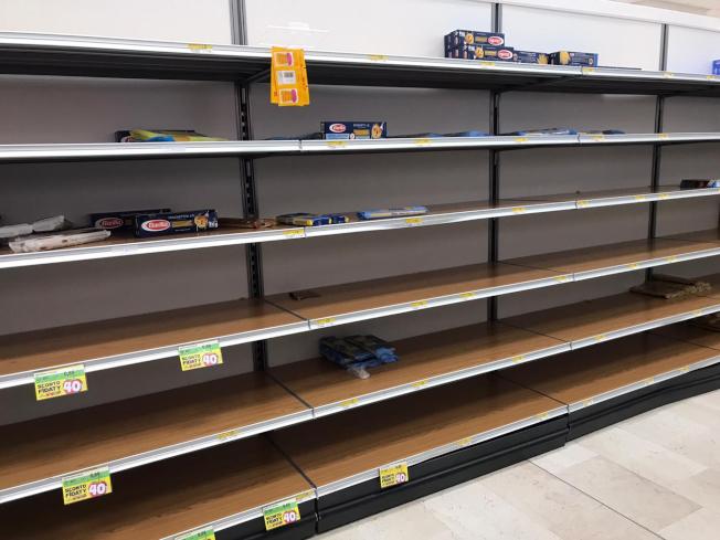 義大利北部靠米蘭的洛札諾市的超市23日都已被購一空,居民擔心疫情大,被迫隔離在家,無法購物。(美聯社)