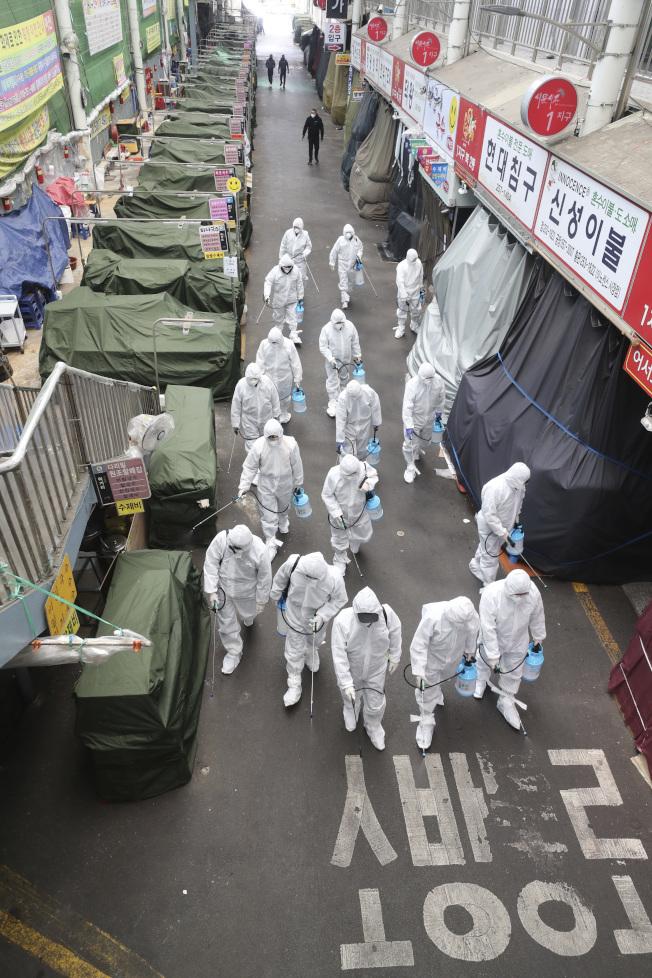 南韓醫療人員23日在疫情最嚴重的大邱地區進行排查式的消毒行動。(美聯社)