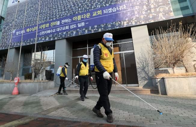 南韓的一個新天地耶穌教會(Shincheonji Church of Jesus)集會建築前,醫療人員在噴灑消毒劑。(Getty Images)