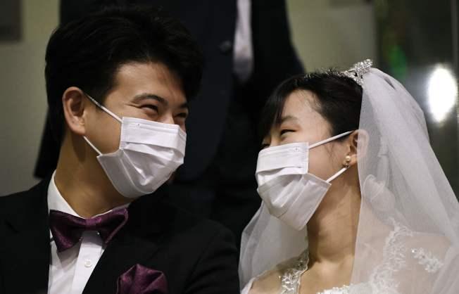 受疫情影響,美國婚紗精品店面臨訂單無法出貨的窘境。圖為疫情嚴重的韓國,近日統一教舉行集體結婚,新人都戴上口罩,以策安全。(Getty Images)