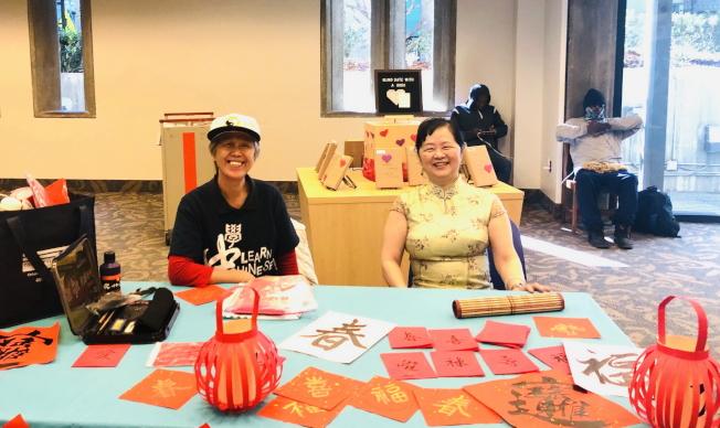 奧蘭多中央圖書館慶春節,書法老師藍碧月(左)示範書法。(中華學校提供)