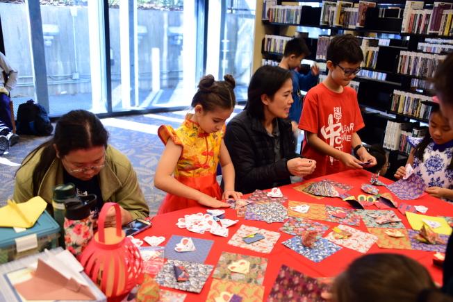 奧蘭多中央圖書館慶春節,謝侑江老師(右二)示範褶紙教學,左一為羅啟珊老師。(中華學校提供)