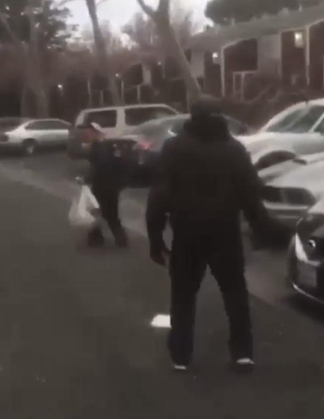 一名非裔男子以長棍多次威脅企圖擊打拾荒的華裔老人,在場有許多非裔圍觀。(記者李秀蘭翻攝)